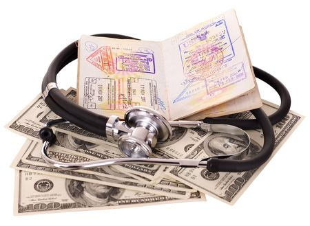Medical still life with stethoscope, money and passport. Isolated. photo