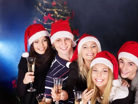 Group young people in santa hat drink champagne outdoor. photo