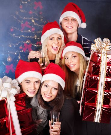 Group  people in santa hat holding stack gift box at nightclub. photo