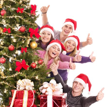 Group of young people in santa hat show thumb. Isolated. Stock Photo