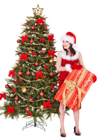 Girl in santa hat holding gift box by christmas tree.  Isolated. photo