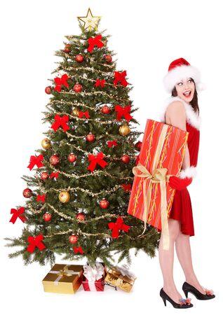 Girl in santa hat holding gift box near christmas tree.  Isolated. photo