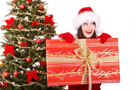 Girl in santa hat holding gift box by christmas tree.  Isolated. Stock Photo - 8405118