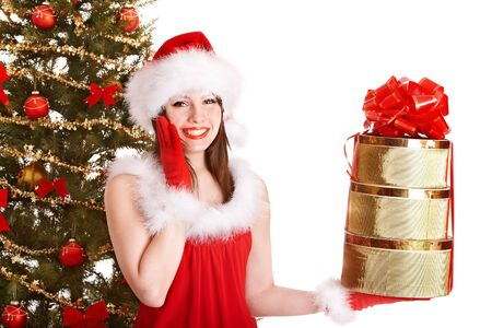 Girl in santa hat holding stack gift box near christmas tree.  Isolated. photo