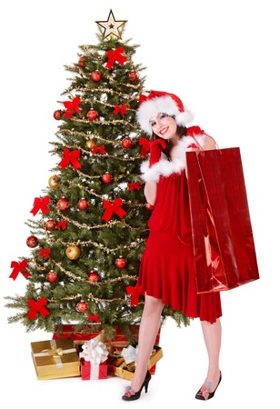 Girl in santa hat holding shopping bag by christmas tree.  Isolated. photo