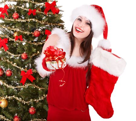 Girl in santa hat holding christmas socks and gift box by christmas tree.  Isolated. photo