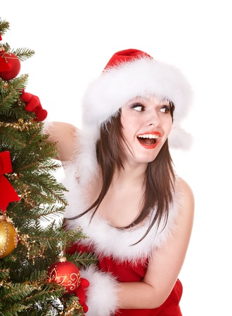 Girl in santa hat holding gift box near christmas tree.  Isolated. photo