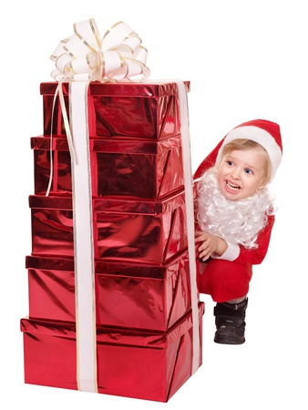 Little girl in santa hat  by stack gift box. Isolated. photo