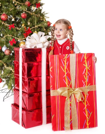 Little girl holding gift box by christmas tree. . Isolated. photo