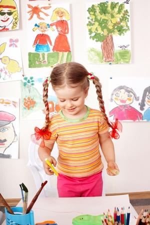 Little girl preschooler painting in classroom. photo