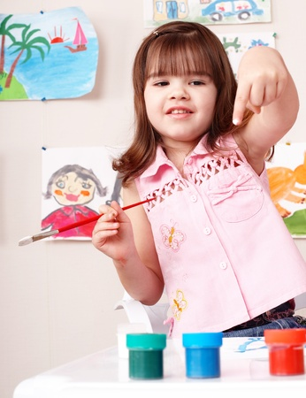 Child with picture and brush in play room. Preschool. Stock Photo - 8332697