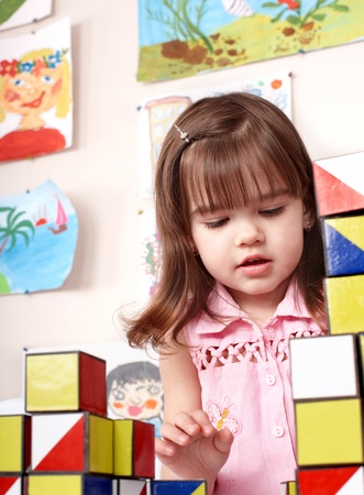 Little girl playing  block  in  preschool. photo