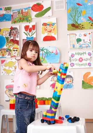 Little girl playing   block and construction set in play room.  Preschool. photo