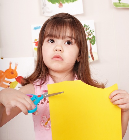 Serious child cutting paper by scissors. photo
