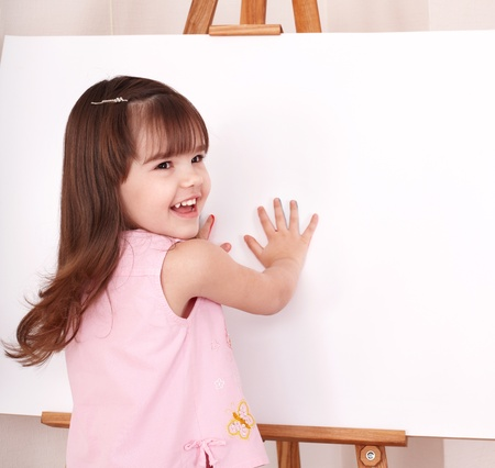 Little girl  making hand prints. photo