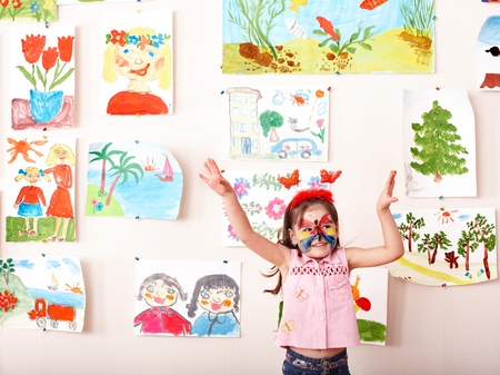 Child with  face painting in play room. Preschooler. photo