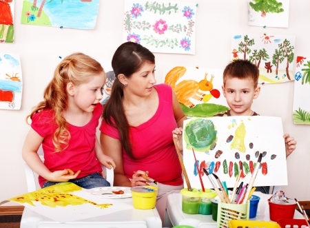 child care:  Child with teacher draw paints in play room. Preschool.