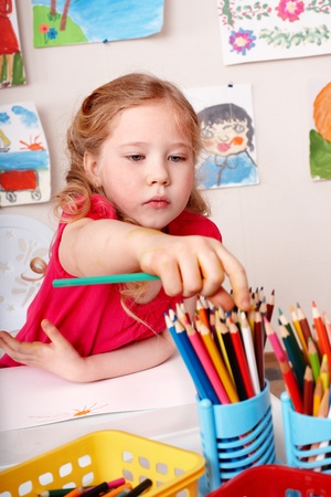 Little girl drawing  pencil in play room. photo