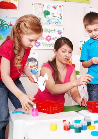 Child with teacher in play room. Preschooler. photo