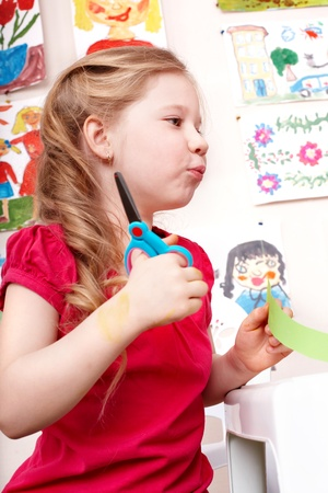 Child with scissors cut paper in play room. Preschool. photo