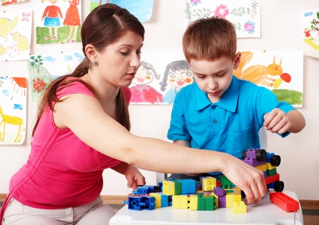 upbringing: Child with construction  in play room. Preschool.