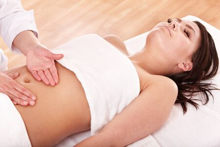 beauty parlour: Beautiful young woman having stomach massage. Stock Photo