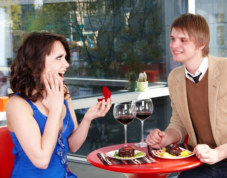 Man propose marriage to girl in restaurant. photo