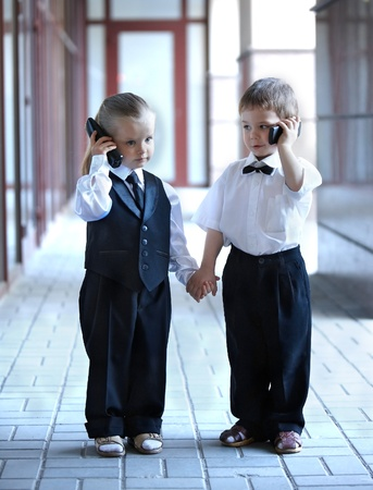 baby in suit: Children in business suit with mobile phone outdoors. Concept.