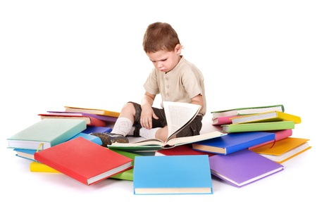 child book: Little boy reading pile of books.