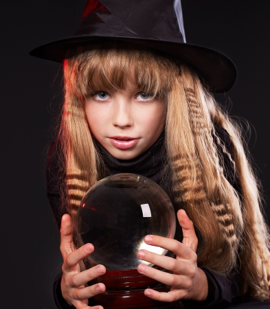Little girl  holding crystal ball. Fortune telling photo