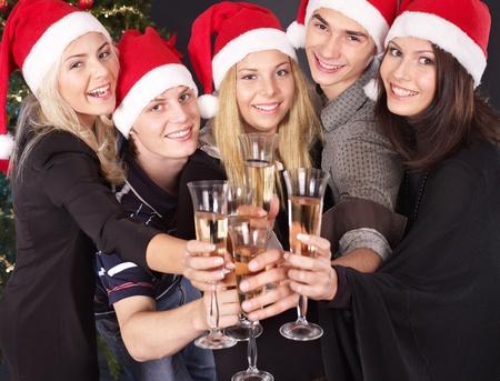 winter party: Gruppo di giovani nel cappello santa bevendo champagne al nightclub. Archivio Fotografico