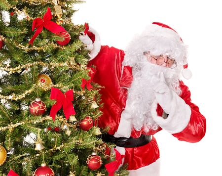 shushing: Santa Claus  making silence gesture by christmas tree. . Isolated.