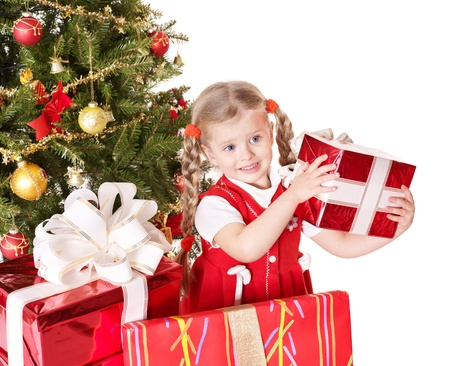 giving season: Happy little girl giving gift box by christmas tree Isolated.