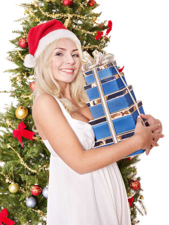 Girl in santa hat holding blue gift box by christmas tree. Isolated. photo