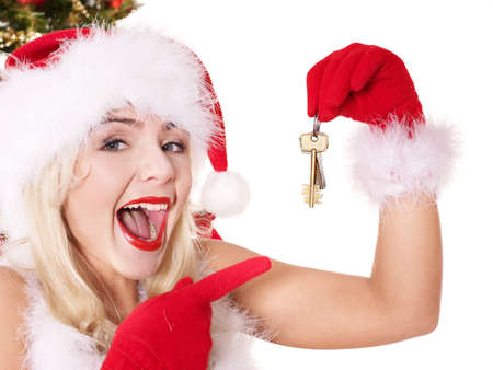 Christmas girl in santa hat holding house keys. Isolated. photo