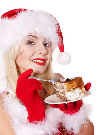 Christmas girl in red santa hat eating cake on plate. Isolated. photo