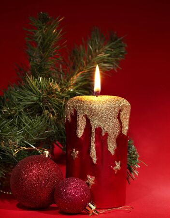 Christmas candle and poinsettia on red. photo