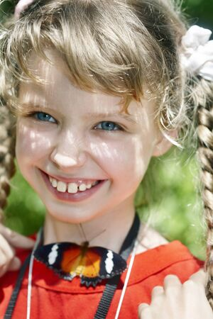 Happy child with butterfly on neck.Nature. photo