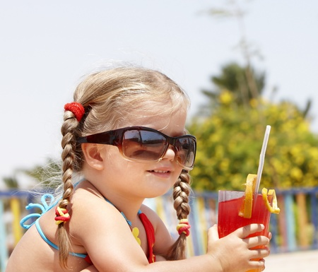 bikini pool: Little girl in glasses and red bikini on playground drink  juice. Stock Photo