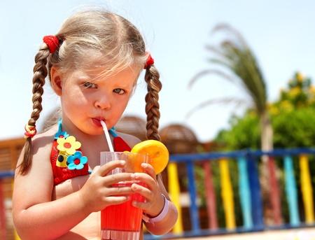 Child girl in glasses and red bikini drink orange juice.