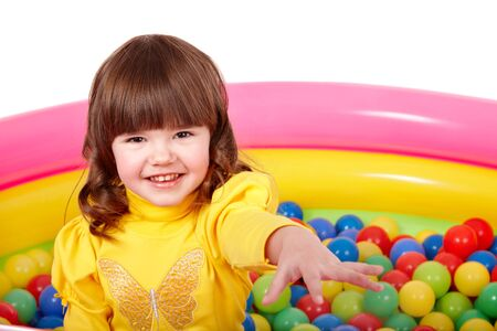 Child in group of colourful ball. Isolated. photo