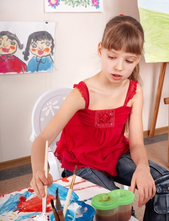 Little girl with picture and brush in playroom. photo