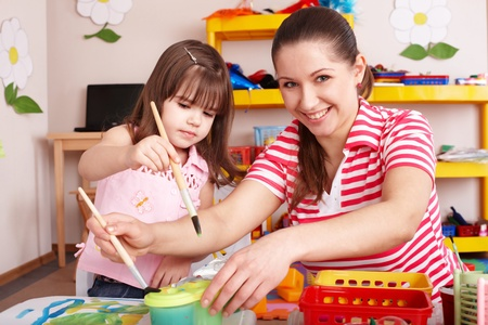 Little girl painting with mother  in preschooler. photo