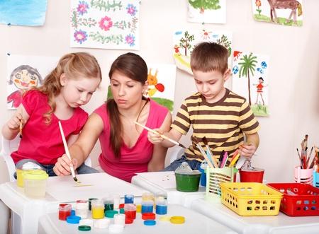 Children with teacher painting in play room. Preschool. photo