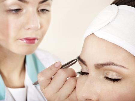 tweezing: Tweezing eyebrow by beautician. Isolated. Stock Photo