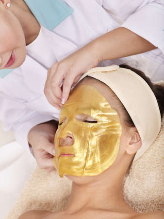 Young womanl with gold facial mask. photo