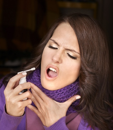 Young woman using throat spray. Stock Photo - 8781840