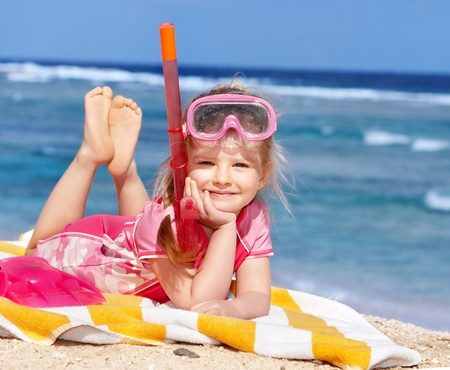 scuba goggles: Little girl  playing on  beach.