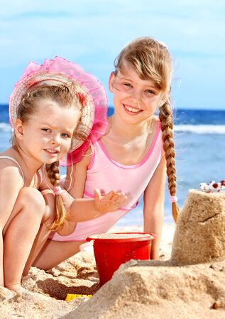 sand castle: Little girl  playing on  beach.