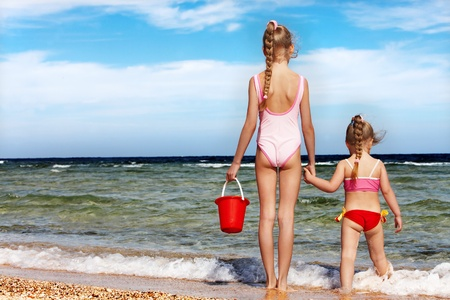 Children holding hands walking on the beach. Rear view. Stock Photo - 8781943